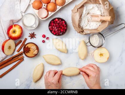 Frau macht hausgemachte Kuchen mit Äpfeln, Preiselbeeren und Zimt auf einem Marmortisch. Das Konzept des Hausbackens. Draufsicht, selektiver Fokus - Stockfoto