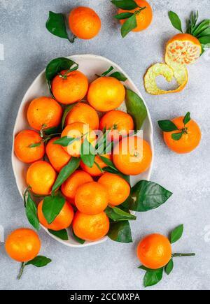 Frische Zitrusfrüchte Mandarine Orangen Frucht (Mandarinen, Clementinen,) mit Blättern in einer hellen Schale auf einem grauen Stein oder Beton Hintergrund. Selektiver Fokus, bis