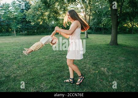 Junge Mutter Spinning Kleinkind Baby Junge im Freien. Eltern spielen mit Kind Sohn im Park. Authentischer Lifestyle lustiger Moment. Happy Family Life Konzept. Ch - Stockfoto