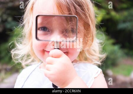 Junges Kind weiblich 3 Jahre alt spielt im Freien in der Wälder mit Vergrößerungsglas auf der Suche nach Insekten und Insekten Zu betrachten