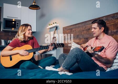 Freund und Freundin spielen die Gitarre, junge kaukasische Paar in der Liebe miteinander im Schlafzimmer.