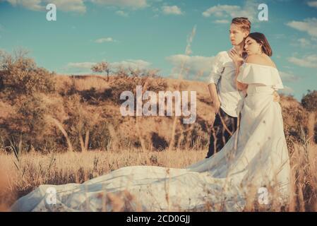 Junge Hochzeit Paar von einem Mann und einem Mädchen, in einem weißen Kleid, auf einem Feld, vor dem Hintergrund eines bewölkten blauen Himmel, Sonnenuntergang. Liebe zum jungen Peop