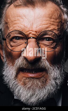 Schwarz-Weiß-Nahaufnahme Porträt eines älteren Mannes mit dunklen bösen Horror-Ausdruck im Gesicht, bedrohlich hohen Kontrast. - Stockfoto