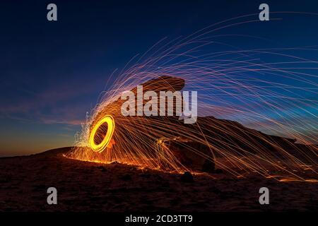 Nachts brennende Stahlwolle (Nachtaufnahmen mit langsamer Verschlusszeit) – selektiv auf das Motiv fokussiert. - Stockfoto