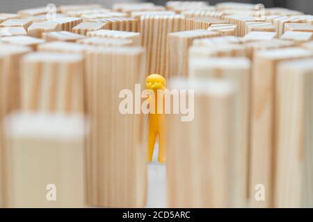 Eine menschliche Figur steht mitten in hohen Mauern. Konzeptfoto, wie hohe Blockaden den Menschen begrenzen. Figur weint. - Stockfoto