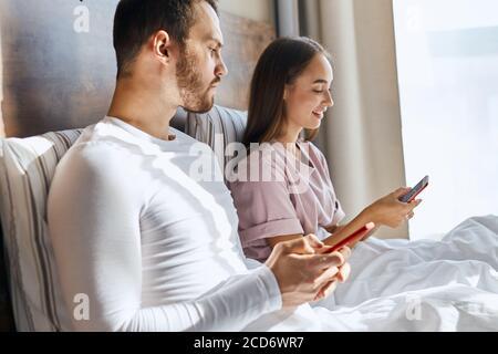 Fröhliche hübsche Frau sitzt auf dem Bett mit Handy in der Hand, gerne SMS mit Freunden im Chat, seriöse unrasiert Mann sitzt in der Nähe von piepend in Telefon - Stockfoto