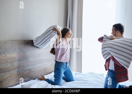 Charmante, überfröhliche Liebhaber, die Spaß zu Hause haben, im Schlafzimmer spielen, fröhlich mit Kissen kämpfen, wegschauen, breit lächeln, glücklichen Ausdruck bringen