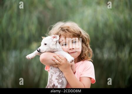 Umarmen Sie Freunde. Glückliches Kind und Hund umarmt sie mit Zärtlichkeit lächelnd.