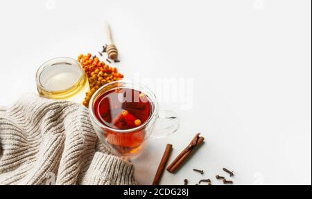 Vitamintee mit Beeren, Honig, Rowan- und Sanddornbeeren, Zimtstangen und trockenen Nelken auf hellem Tisch mit gestricktem beigen Pullover. Nützlicher Profi - Stockfoto