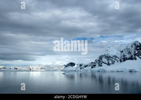 Gebirgskette in der Antarktis bedeckt mit Schnee und Eis mit Eisbergen, die im Ozean schwimmen.