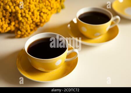 Zwei gelbe Kaffeetassen auf weißem Hintergrund, Kaffeepause und Koffein sucht Konzept. Gelbe Blumen auf dem Tisch Stockfoto