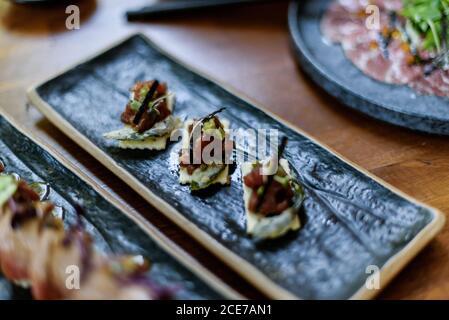 Hoher Winkel von köstlichem Sushi mit gehacktem Lachs auf gelegt Teller auf dem Tisch im Restaurant
