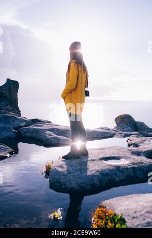 Rückansicht einer Frau, die auf einem Stein gegen die Sonne steht und auf das Meer blickt. - Stockfoto