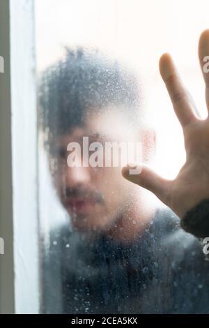 Mann hinter dampfenden Glas mit den Händen darauf - Stockfoto