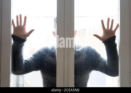 Aufnahme eines Mannes im Pullover, der hinter nassem, dampfendem Glas steht Die Tür hält die Hände darauf - Stockfoto