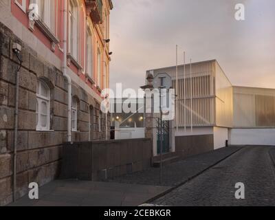 Malerischer Blick auf die alte verputzte Wand des mehrstöckigen Gebäudes und Leere dunkle Straße bei Sonnenuntergang