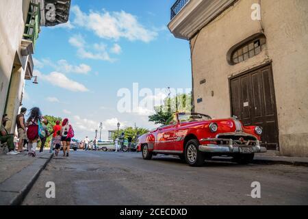 LA HABANA, KUBA - 6. NOVEMBER , 2018: Vinous vintage Cabriolet auf der Straße in der Nähe von Wanderern an sonnigen Tagen in Kuba