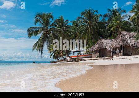 Malerischer Blick auf Hütten, Boot und tropischen Wald am Sandstrand in der Nähe von Meer und blauen Himmel in San Blas Inseln, Panama