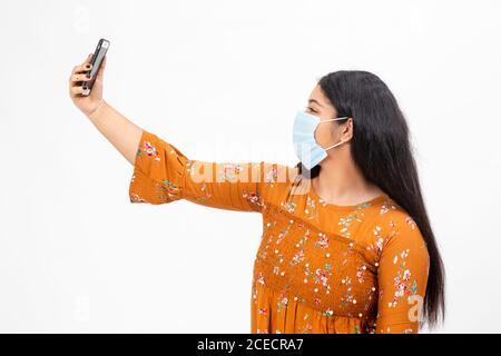 Junge indische Mädchen trägt eine Gesichtsmaske und nutzt sie Smartphone, um ein Selfie zu machen - Stockfoto