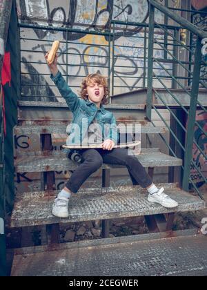 Kind mit Skateboard auf Treppen sitzen