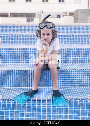 Konzept der wehmütigen Kind mit Schnorchelmaske und Flossen in t-Shirt und Shorts sitzen auf Treppen von leeren blauen Schwimmen Pool