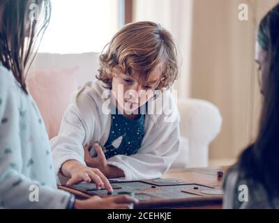Adorable junge im Bademantel spielen gute Brettspiel mit anonymen Familie in stilvollem Zimmer