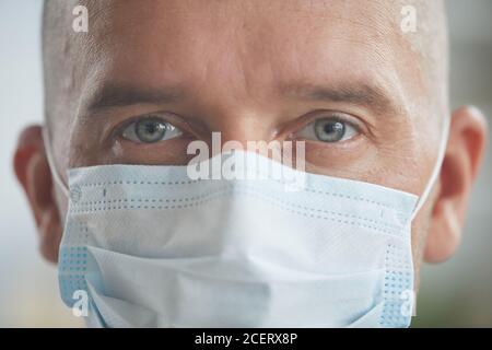 Horizontale Nahaufnahme Portriat Aufnahme von unkenntlichen kaukasischen Mann trägt Schutz Maske auf seinem Gesicht und Blick auf die Kamera
