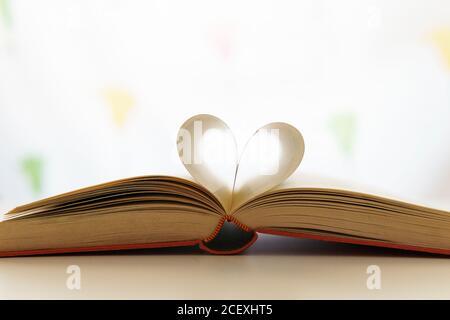 Nahaufnahme eines geöffneten Buches mit Seiten in Herzform Platziert auf einem Tisch im hellen Raum