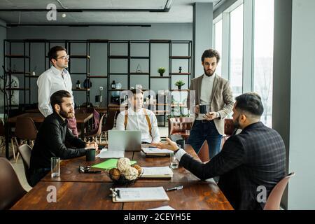 Junge kaukasische Unternehmer versammelten sich im Büro für Coworking, halten Treffen für Diskussionen und effektive Zusammenarbeit, alle in f gekleidet - Stockfoto