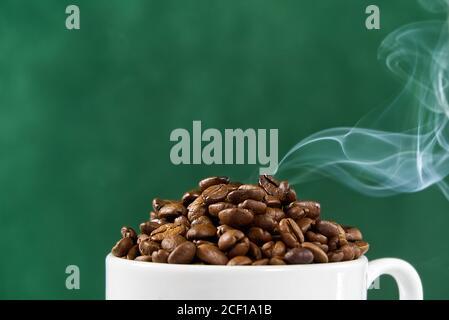 Internationaler Tag des Kaffees Konzept. Nahaufnahme weiße Kaffeetasse voller Kaffeebohnen auf grünem Hintergrund mit Rauch auf der Oberseite. Stockfoto