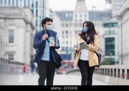 Geschäftsleute in Gesichtsmasken sprechen auf städtischen Fußgängerbrücke - Stockfoto