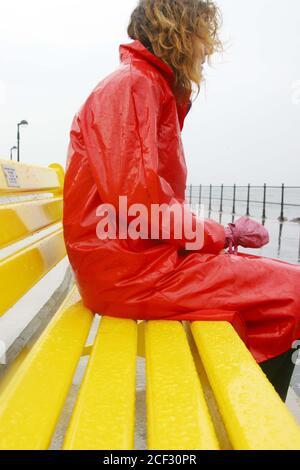 Largs, Ayrshire, Scotland 15 Nov 2003 : Frau in rotem Regenmantel, gekauft von einem Wohltätigkeitsgeschäft, kämpft gegen Wind und Regen auf der neuen Promenade. Auf einer gelben Bank sitzend, lief Regen über ihren Mantel - Stockfoto