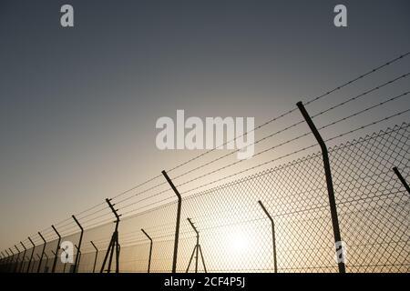 Metall-Sicherheitszaun vor wolkenlosem Himmel mit Helle Sonne