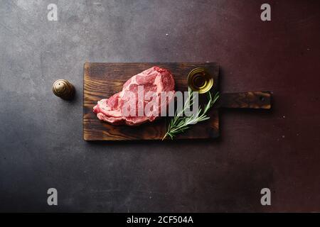 Draufsicht auf rohes schwarzes angus Prime Rib Eye Beef Steak auf Holzschneidebrett. - Stockfoto
