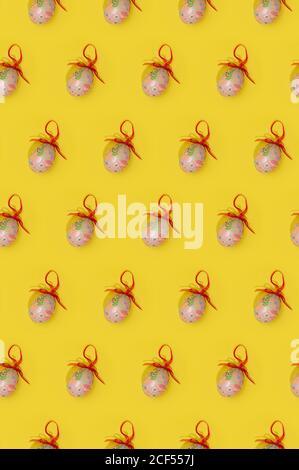 Nahtloses Ostermuster mit bunten Eiern verziert mit roten Bändern In Reihen auf gelbem Hintergrund angeordnet Stockfoto
