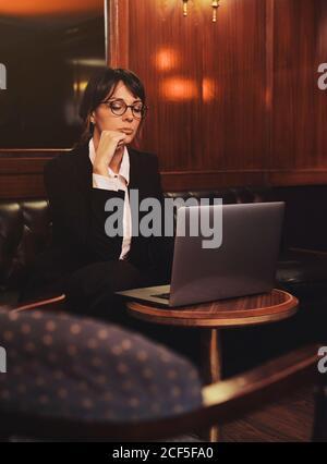 Smart Business Frau in Brille tippen auf Laptop bequem sitzen In schwarzem Ledersofa im Café - Stockfoto