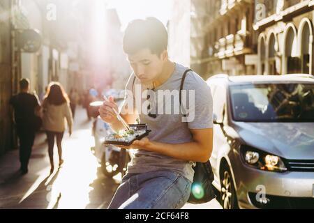 Schöner ethnischer asiatischer Mann, der Essen zum Mitnehmen isst, während er dabei steht Foodtruck auf sonniger Straße