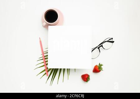 Draufsicht auf leeres Papier und Tasse heißen Kaffee Auf weißem Schreibtisch mit stilvoller Brille und frischen Erdbeeren - Stockfoto