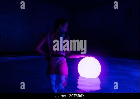 Rückansicht der schlanken Frau im Badeanzug im Dunkeln stehend Thermalbad mit leuchtendem Ball auf dem Wasser