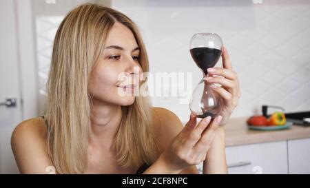 Frau schaut auf die Sanduhr und lächelt. Sie in einer hellen Küche und wartet, Zeitkonzept - Stockfoto
