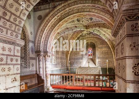 Die normannische Kirche St. George im Cotswold-Dorf Hampnet zeigt den Chor aus dem 12. Jahrhundert, der in den 1870er Jahren vom damaligen Vikar dekoriert wurde. Stockfoto