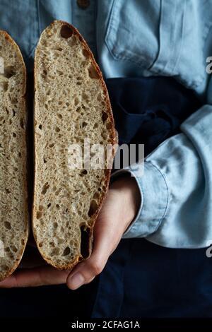 Anonyme Ernte Hand Frau in Schürze halten Scheibe hausgemachten Sauerteig Brot und Laib Brot - Stockfoto