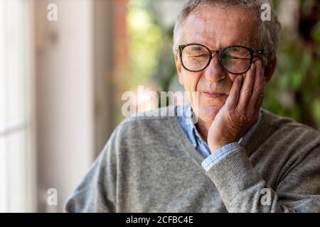 Älterer Mann, der Zahnschmerzen hat