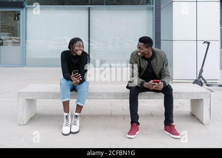 Ganzkörper junge afroamerikanische Mann und Frau mit Smartphones Lächelnd und einander anschauend, während sie auf der Bank sitzen Und Bekanntschaft machen auf der modernen Stadtstraße - Stockfoto