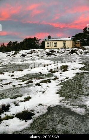 Landhaus in holprigen schmelzenden schneebedeckten Feld und Wald Silhouette bei Dämmerung Stockfoto