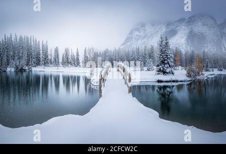 Wunderschöne kanadische Winterlandschaft mit schneebedeckter Brücke über Ruhe Wasser mit Tannenwald und nebligen schneebedeckten Bergen im Hintergrund Stockfoto
