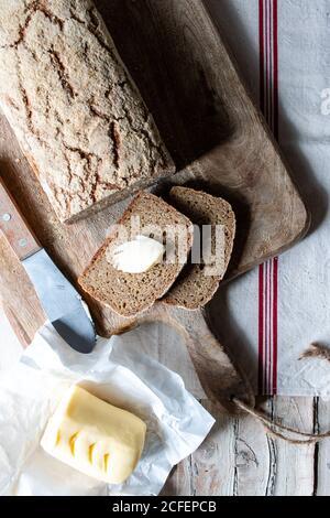 Von oben Laib des leckeren Ryocornbrotes auf Tuch gelegt Serviette neben Löffel Korn auf Holzhintergrund