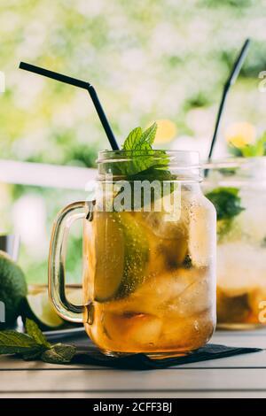 Mojito-Cocktail mit Limette, Minze, Rum, Soda und Eis in Einmachglas mit natürlichem Licht, im Freien zubereitet Stockfoto
