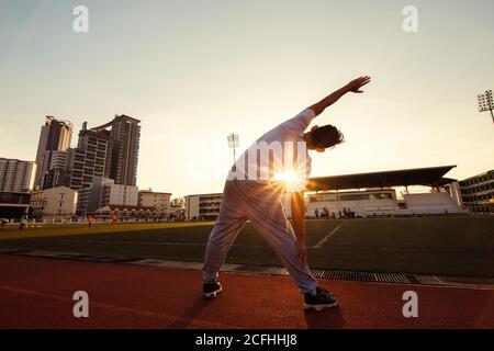 Ganzkörperporträt eines sportlichen Mannes, der sich im Sportstadion ausdehnt.