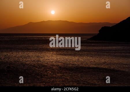 Friedliche Landschaft von Meer und Bergkette unter Himmel mit Toller orangefarbener Sonnenuntergang
